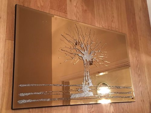 Silver glitter tree on bronze mirror .